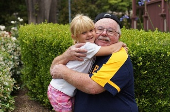 A man with glasses and a backwards baseball cap hugs his granddaughter outside