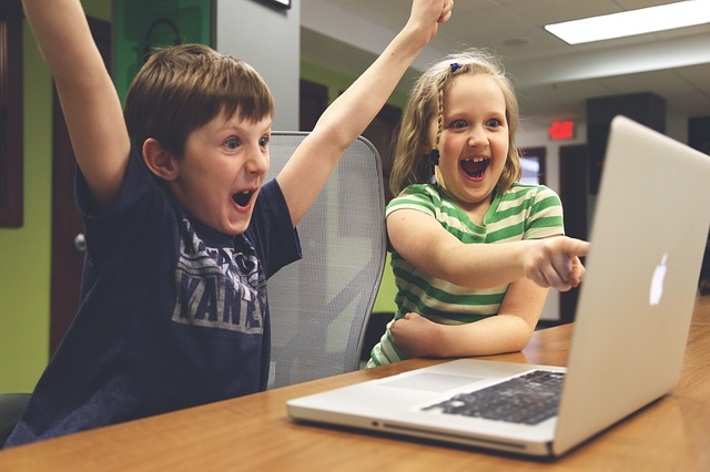 a young girl and boy cheer in front of a Mac as they play a video game